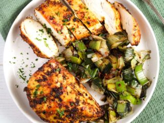 air fryer chicken breast no breading sliced on a white plate.