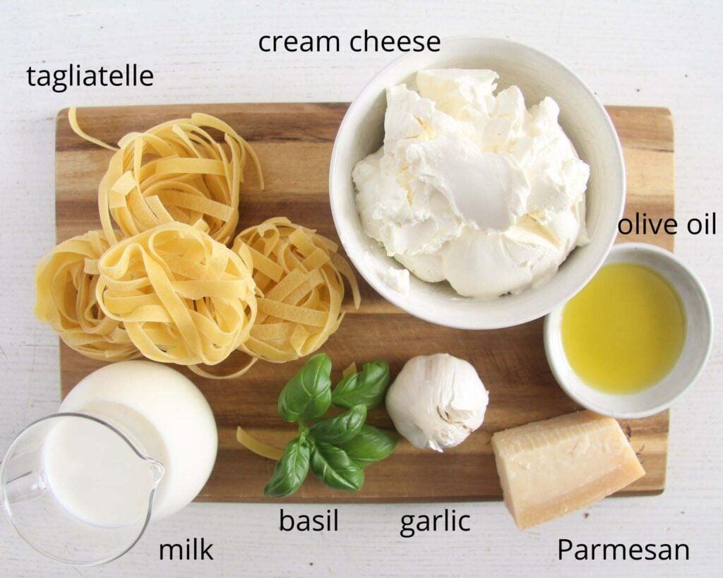 tagliatelle, cream cheese, oil, basil, garlic, milk, parmesan on a wooden board.