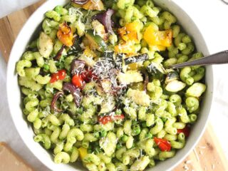 vegetable pesto pasta with parmesan in a white bowl