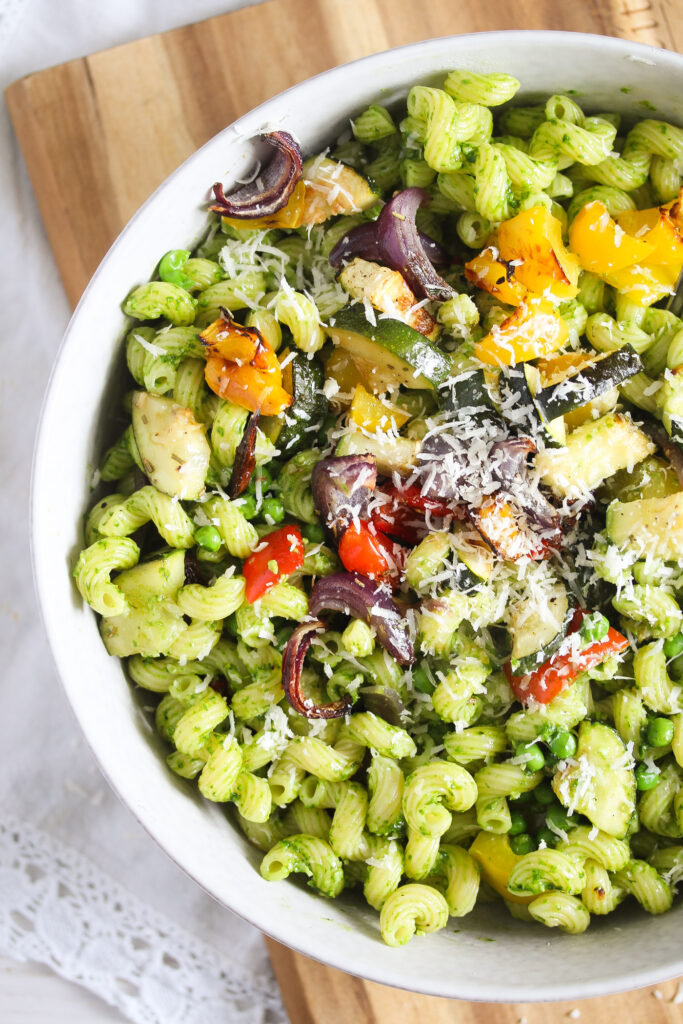 veggie pasta with pesto and parmesan in a white bowl