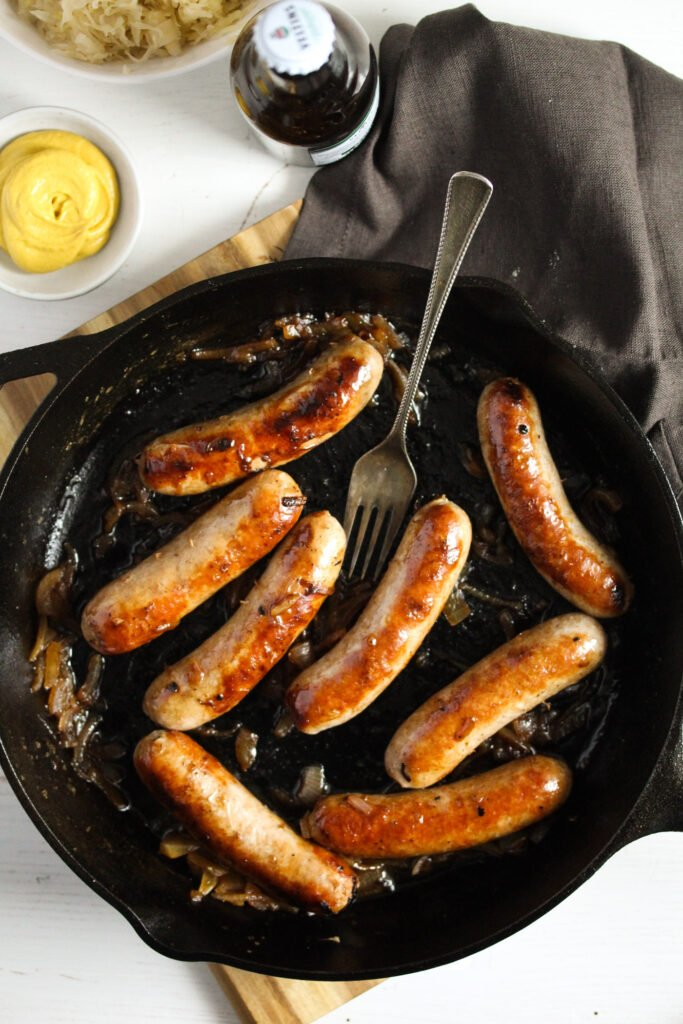 brats in a pan served with a bowl of mustard.