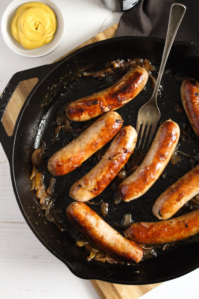 overhead shot of a black pan with bratwurst in it.