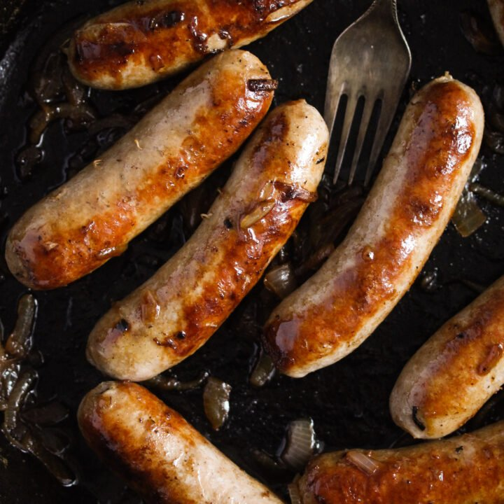 seven sausages in a cast iron pan with a fork.
