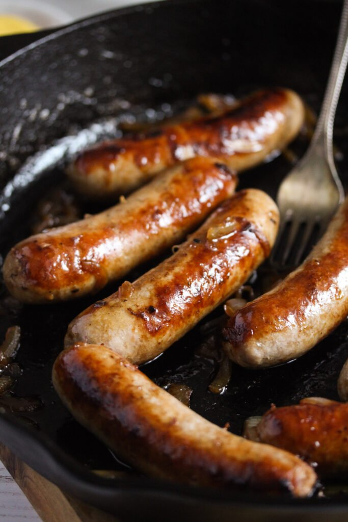 brown sausages in a cast iron pan.