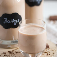 homemade irish cream in a small glass and bottles