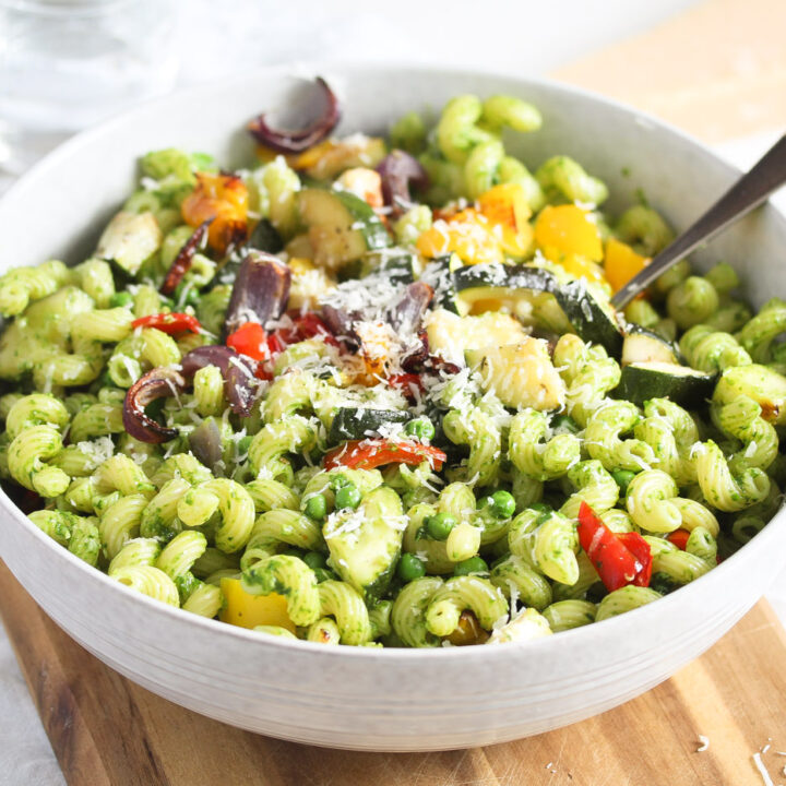 pesto vegetable pasta in a small white bowl with a spoon in it