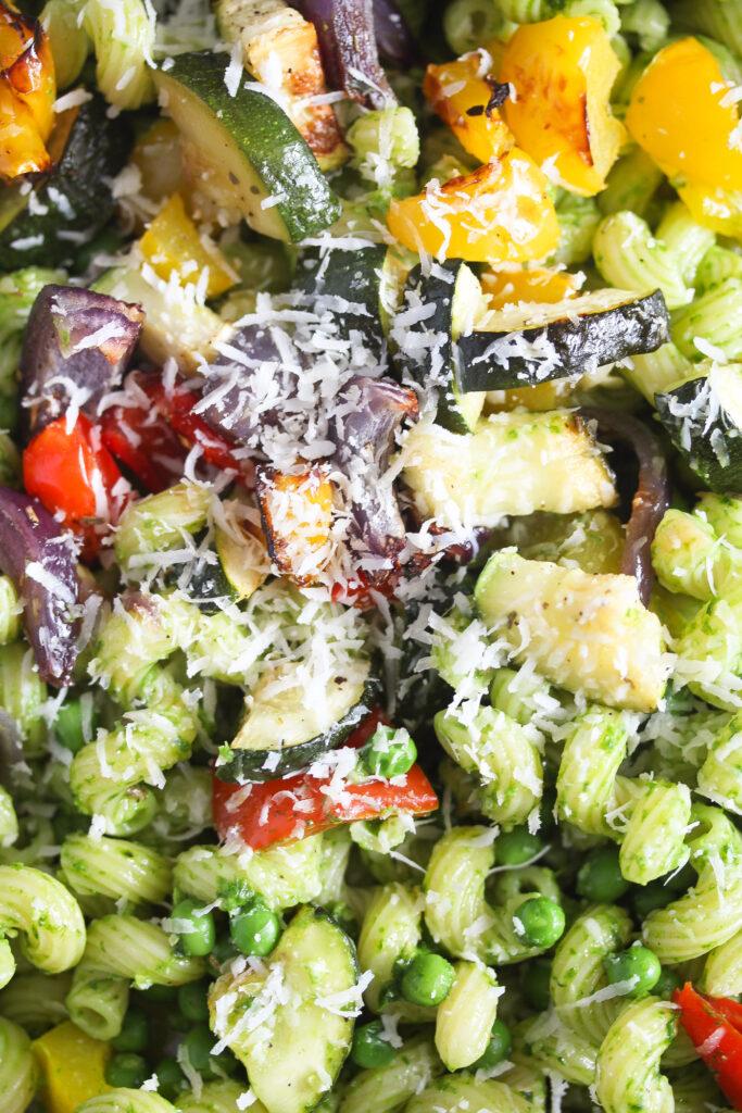 close up green noodles, veg and parmesan