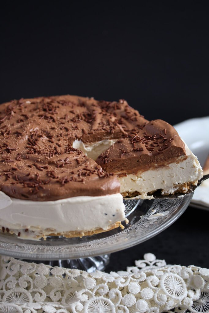 slicing a cheesecake topped with chocolate cream.