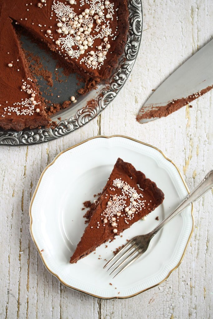 overhead picture of a chocolate tart on a platter and on a plate.