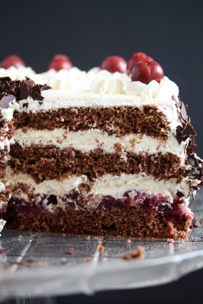 close up layers of chocolate cake with cherries and cream.