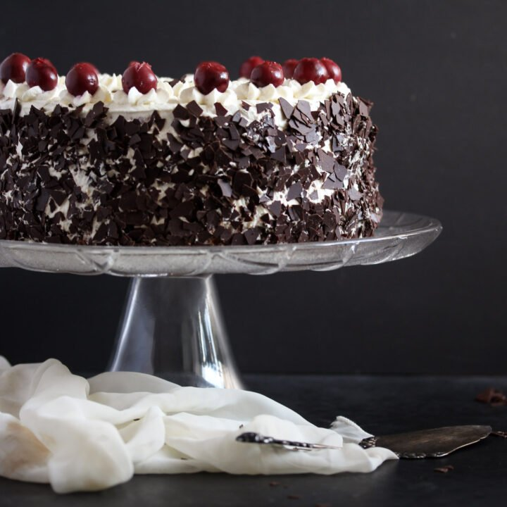 black forest gateau on a platter decorated with cherries.