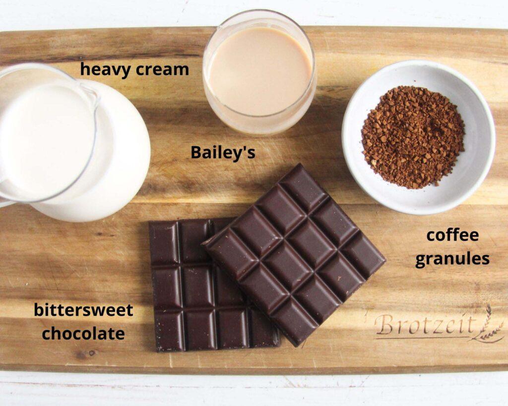 cream, baileys, coffee granules, chocolate on a chopping board.