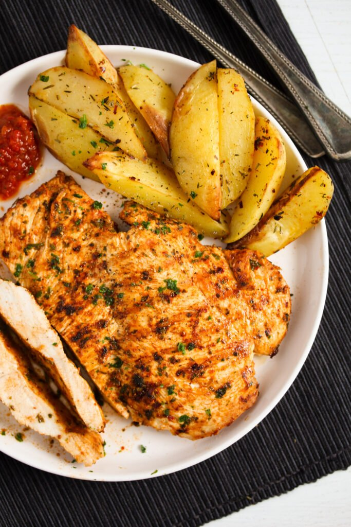 sliced grilled nando's chicken breast with oven potatoes and dip.