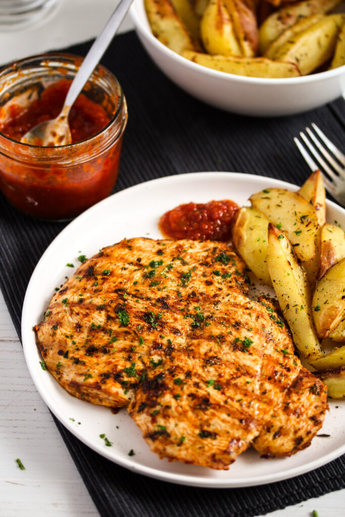 plate with peri peri chicken, potatoes and sauce.