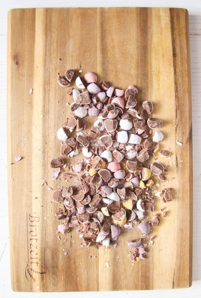 cadbury chocolate eggs crushed on a chopping board.