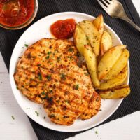 nando's butterfly chicken served with potatoes on a white plate.