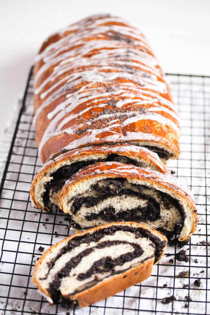 sliced poppy seed roll on a wire rack.