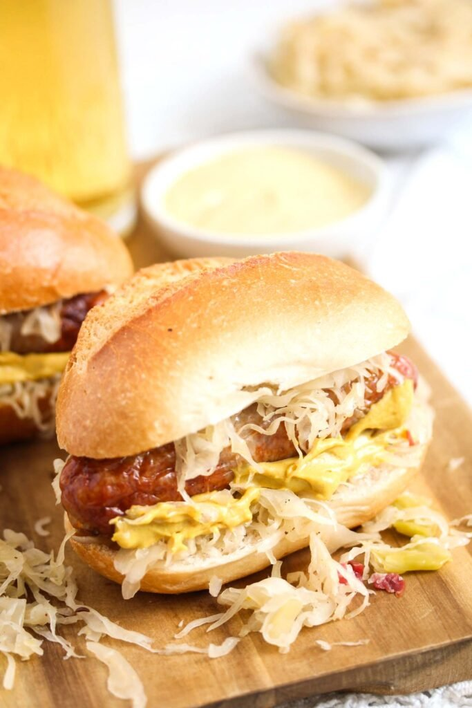 bratwurst bun, mustard and beer on a wooden board.
