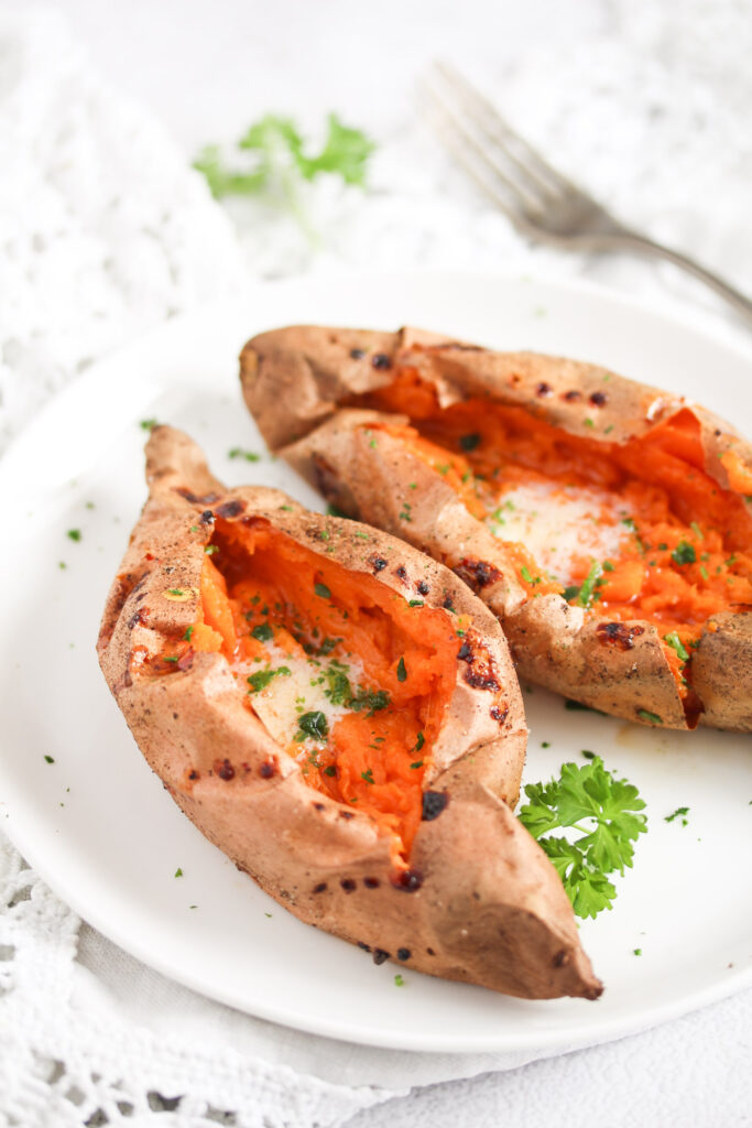 two split sweet potatoes served with melting butter.