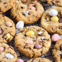 mini egg cookies crowded on a rack.