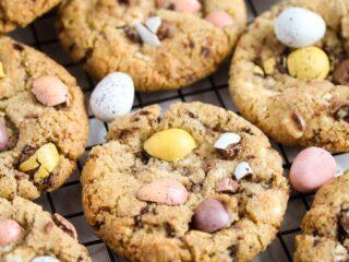 mini egg cookies crowded on a rack.