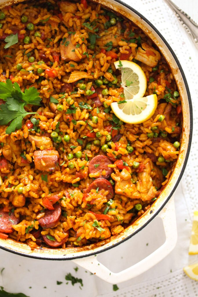chorizo chicken paella garnished with parsley and lemon wedges in a white pot.
