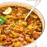spanish rice with chicken and sausage in a white pot.