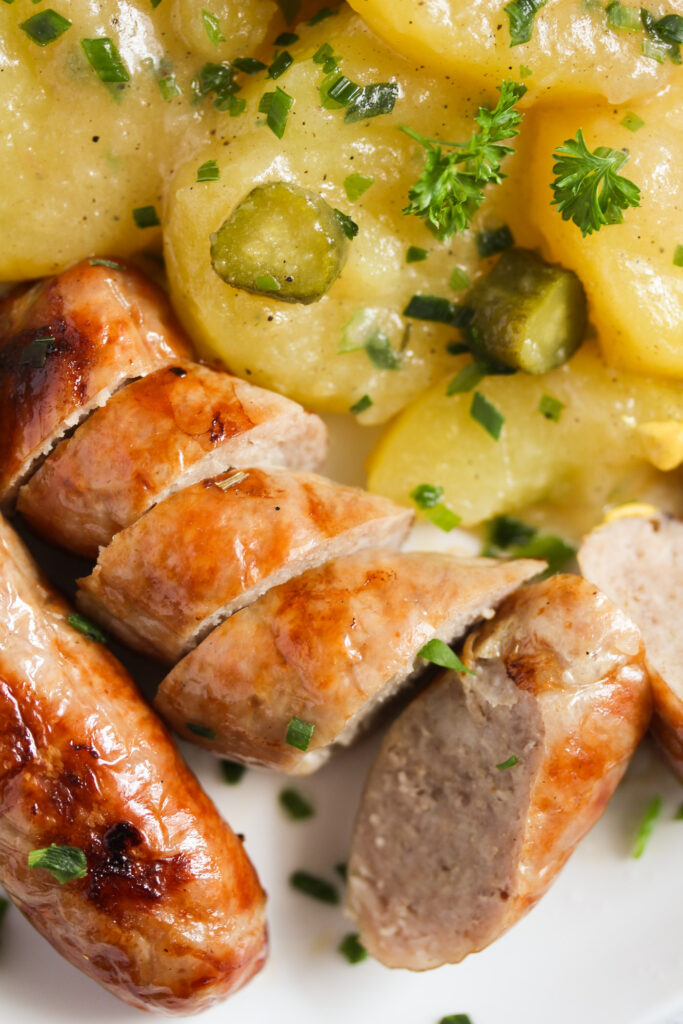 close up bratwurst and potato salad.