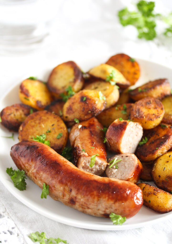 plate with sausages, roasted potatoes and parsley.