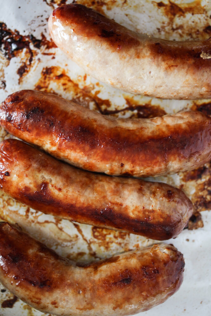 browned sausages on a baking tray lined with foil.
