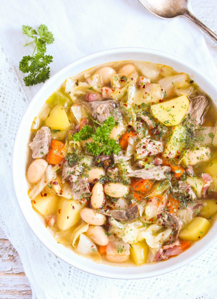 soup made with lamb bone, vegetables and beans in a bowl.