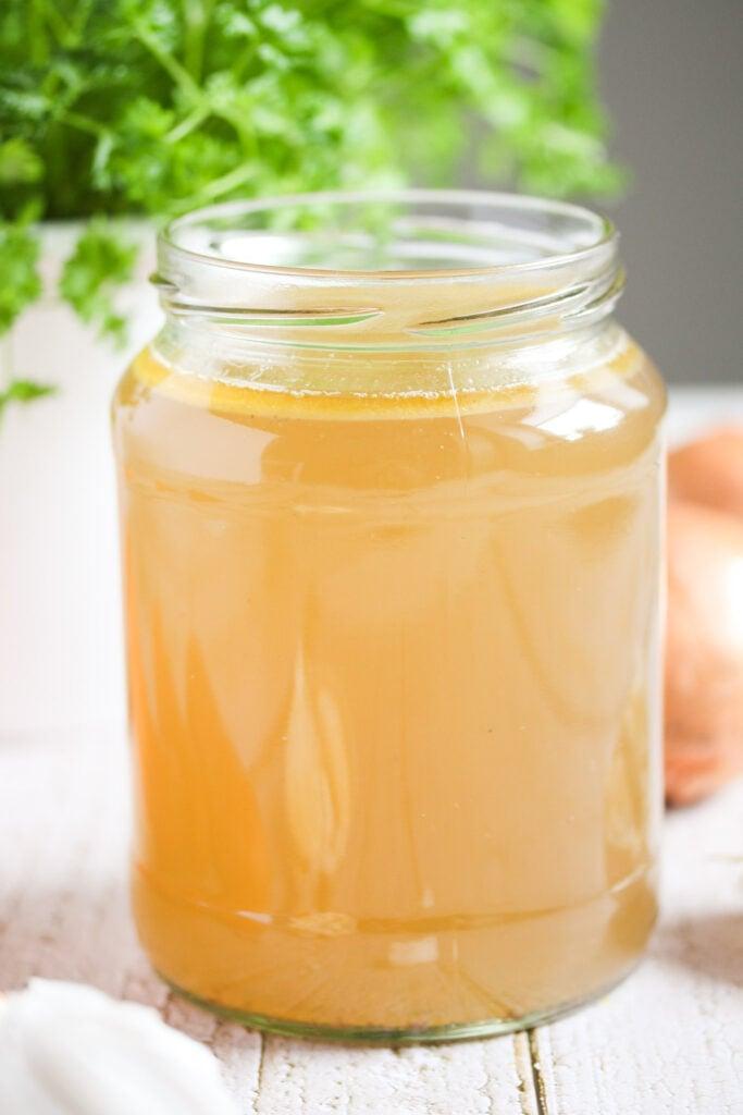 large jar full of homemade stock.