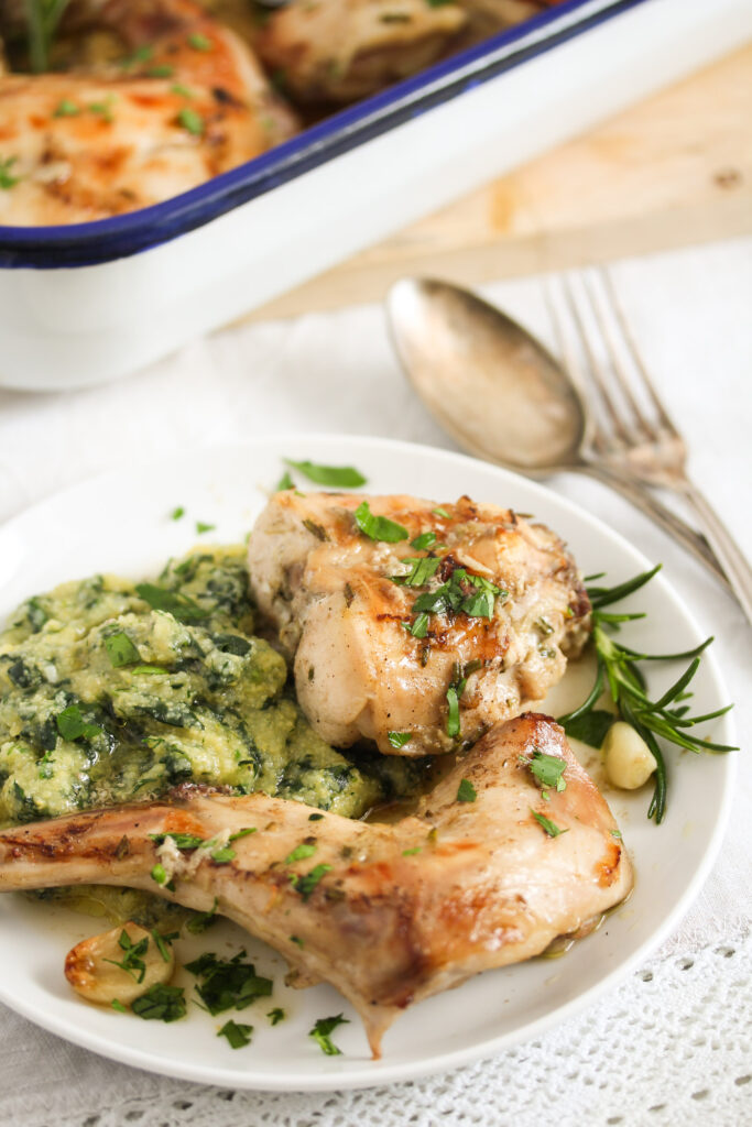 oven cooked rabbit with spinach polenta on a plate.