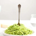 plate of spaghetti with green sauce.