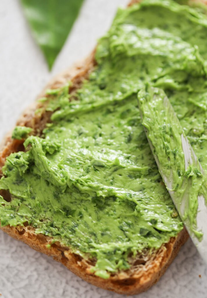 slice of bread slathered with green butter.
