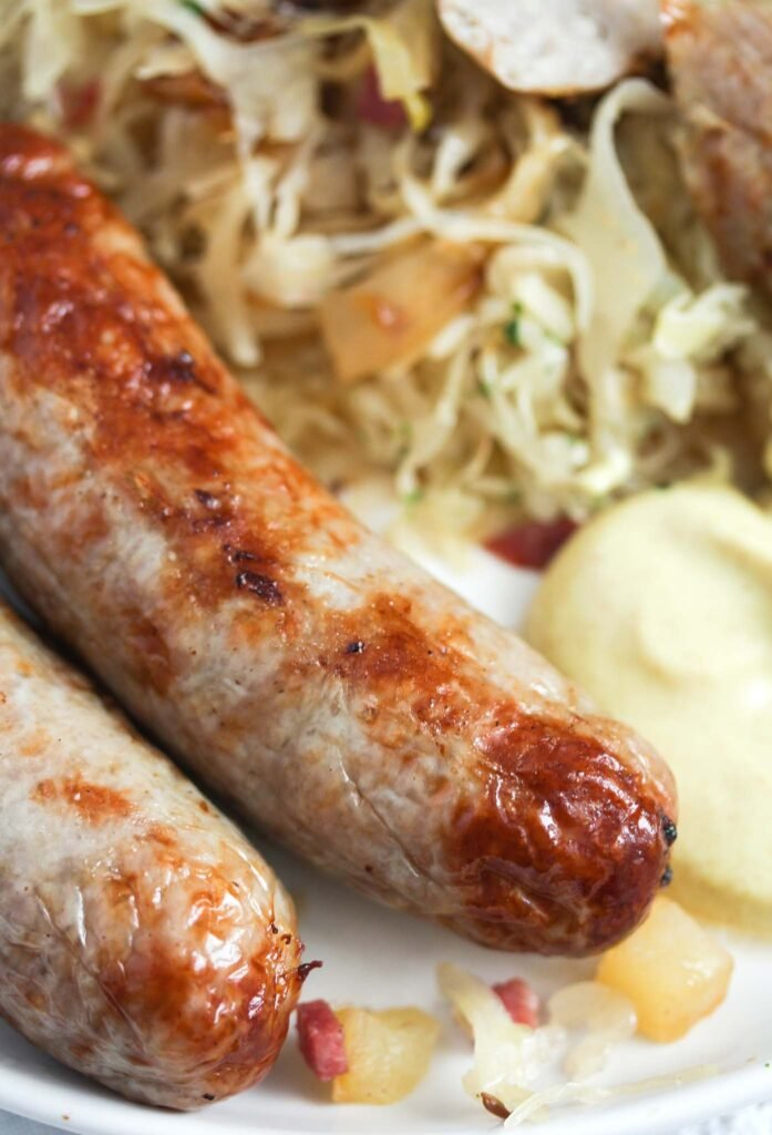 two brats and sauerkraut on a plate served with mustard.