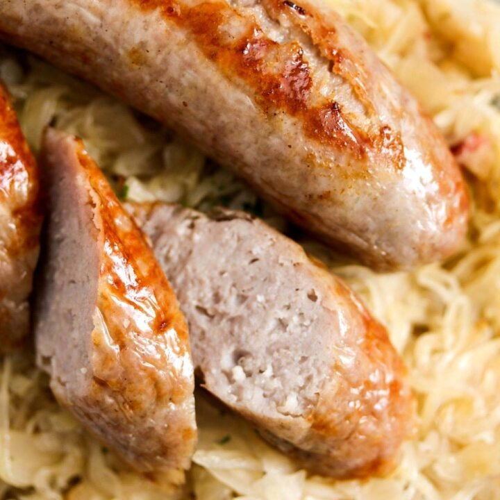 brats with sauerkraut, one sausage sliced, close up on a plate.