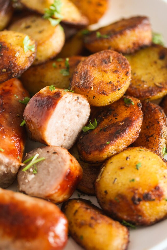 close up of fried potato slices and sliced brats sprinkled with parsley.