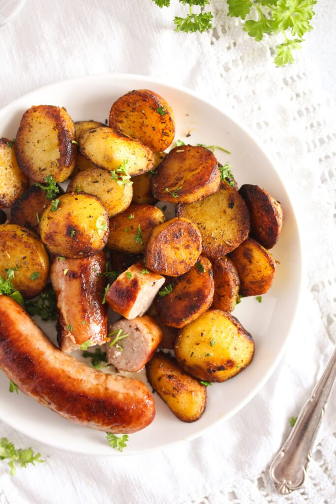brats and fried potatoes on a small white plate overhead image.