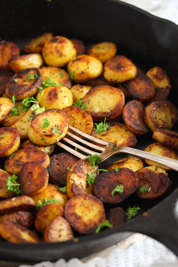 skillet fried potatoes sprinkled with parsley, with a vintage fork.