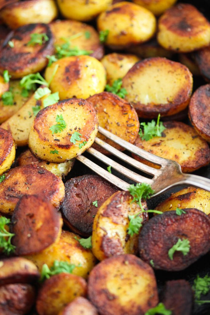 close up golden slices of potatoes fried in pan with a fork on top.