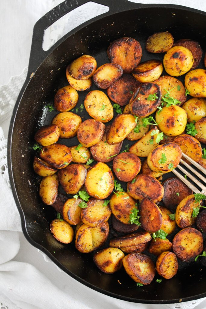 many small potatoes in a heavy-bottomed cast iron pan with a fork.