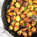 pinterest image of small potato slices fried in a cast iron pan.