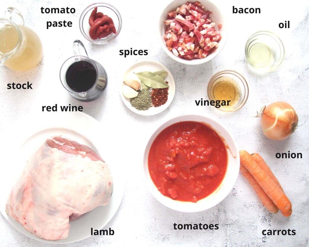ingredients for lamb ragu. stock, tomato paste, tomatoes, bacon, wine, spices, lamb shoulder, vinegar, oil, carrots, onion.
