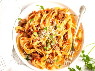 slow cooker lamb ragu with pasta on a small white plate with a silver fork.