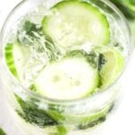 pinterest image for alcoholic drink with cucumbers inside.