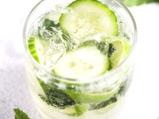 glass of gin mojito with cucumber and lime slices.