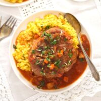 slow cooker ossobuco served with risotto milanese and gremolata.