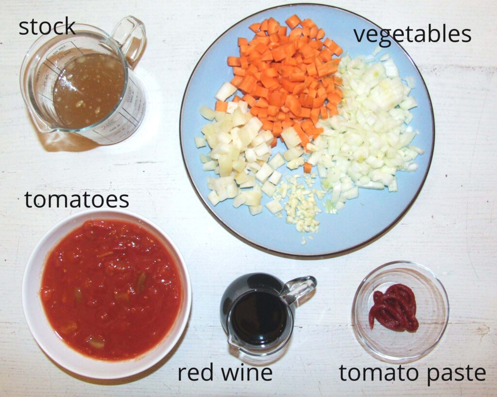 stock, diced vegetables, canned tomatoes, red wine, tomato paste. all in small containers arranged on the table.