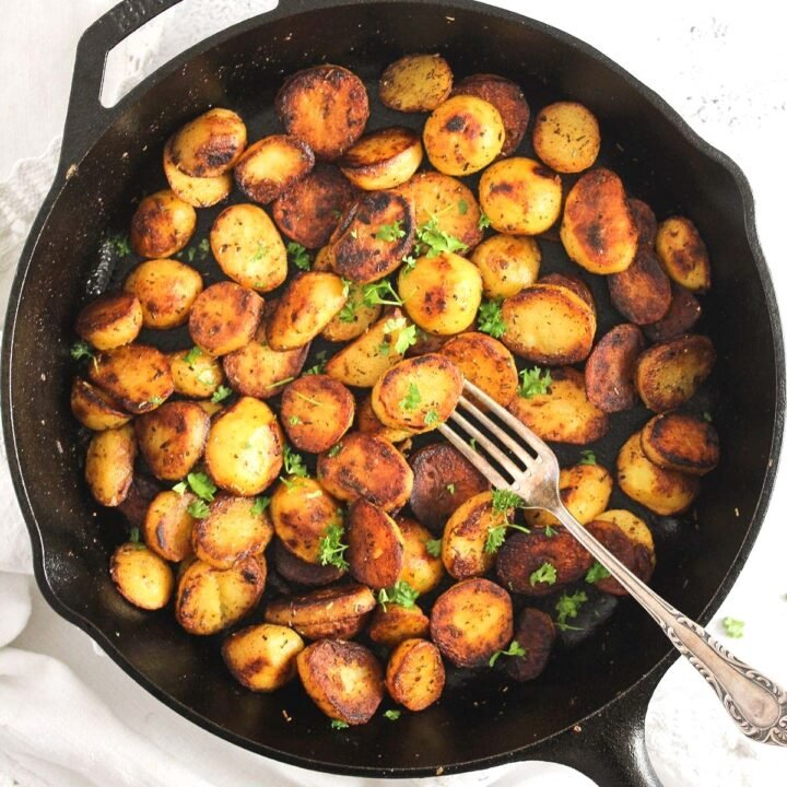 cast-iron skillet potatoes sprinkled with parsley, overhead image.